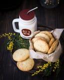 Eigengemaakte die koekjes met sesamzaden en pijnboomnoten, met mimosabloemen worden verfraaid royalty-vrije stock afbeelding