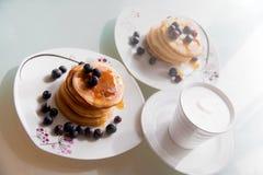 Eigengemaakte die pannekoekplaten door ahornstroop, kaneel en bosbessen op witte platen met kop van heerlijke koffie met room wor royalty-vrije stock afbeelding