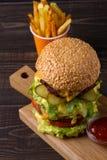 Eigengemaakte drievoudige dekhamburger en gebraden gerechten op donkere houten achtergrond Stock Foto