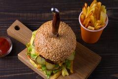 Eigengemaakte drievoudige dekhamburger en gebraden gerechten op donkere houten achtergrond Stock Afbeeldingen