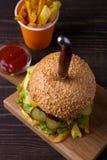 Eigengemaakte drievoudige dekhamburger en gebraden gerechten op donkere houten achtergrond Royalty-vrije Stock Foto's
