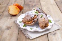 Eigengemaakte gebakjes met dadelpruimen, voor ontbijt, een witte schotel op een servet Houten lijst Vrije Ruimte voor Tekst of Re stock fotografie