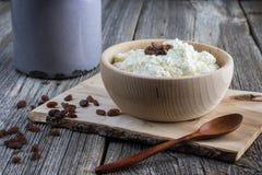 Eigengemaakte gestremde melk in een houten kom met rozijnen en houten lepel royalty-vrije stock foto