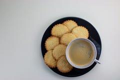 Eigengemaakte gevormde zandkoeken op de zwarte plaat en de kop met zwarte koffie Jonge geitjeshand die één koekje houden Hoogste  stock afbeelding