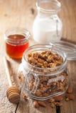 Eigengemaakte gezonde granola in glaskruik en honing Stock Afbeeldingen