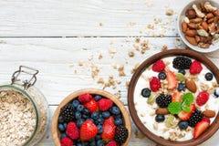 Eigengemaakte granola met Griekse yoghurt, noten en verse bessen in een kom met graangewas in ja Stock Foto's