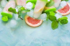 Eigengemaakte grapefruitijslollys met grapefruitplakken op een munt houten achtergrond Royalty-vrije Stock Foto's