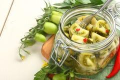 Eigengemaakte groene tomatendomeinen in glaskruik Stock Foto