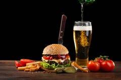 Eigengemaakte hamburger met frieten en fles bier het gieten in een glas Fastfood op donkere achtergrond op houten lijst royalty-vrije stock fotografie