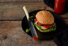 Eigengemaakte hamburger met rundvlees, salade en tomatensaus op een zwarte pla Royalty-vrije Stock Foto