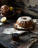 Eigengemaakte heerlijke bundtcake met gat met witte glans op bovenkant op houten tribune stock foto