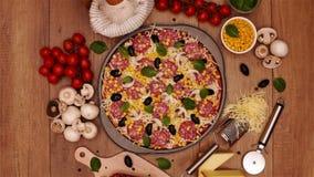 Eigengemaakte heerlijke pizza in ronde pan met verse ingrediënten rond op de lijst stock videobeelden