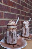 Eigengemaakte hete chocolade, met slagroom en chocoladepoederbovenste laagjes stock afbeeldingen