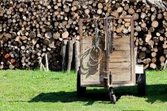 Eigengemaakte houten die landbouwtrekkeraanhangwagen in binnenplaats op ongesneden gras met gestapeld brandhout op achtergrond wo stock fotografie