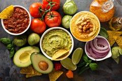 Eigengemaakte hummus, salsa en guacamole met graanspaanders Stock Afbeeldingen
