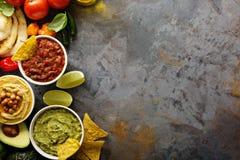 Eigengemaakte hummus, salsa en guacamole met graanspaanders Royalty-vrije Stock Foto