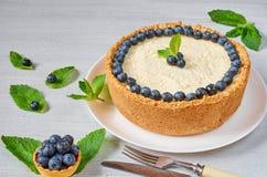 Eigengemaakte kaastaart met verse bessen op de witte die plaat met bosbessen, munt, mes en vork op de grijze lijst wordt verfraai stock foto's