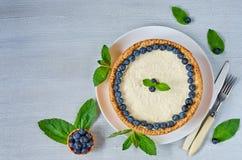 Eigengemaakte kaastaart met verse bessen op de witte die plaat met bosbessen, muntbladeren op de grijze lijst wordt verfraaid stock foto's
