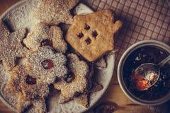 Eigengemaakte Kerstmispeperkoek en linzer koekjes met jam, gepoederde, hoogste vlakke mening, zacht neveleffect, wijnoogst royalty-vrije stock foto's