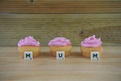 Eigengemaakte kleine cakes voor moedersdag met brieven voor het woord mum stock foto