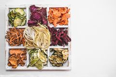 Eigengemaakte kleurrijke spaanders van verschillende verse groenten in een witte houten doos op een witte achtergrond De ruimte v Stock Fotografie