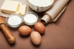 Eigengemaakte koekjesvoorbereiding, bloem, eieren, boter, suiker op een bruine achtergrond stock fotografie