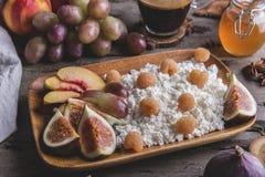 Eigengemaakte kwark, frambozen, fig., perzik, honing gezond ontbijt, koffie bij het dienen van raad over rustieke houten royalty-vrije stock foto