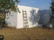 Eigengemaakte ladder tegen witte muur stock afbeelding