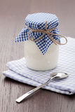Eigengemaakte melkyoghurt in glaspot en lepel op lijst Royalty-vrije Stock Afbeelding