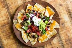 Eigengemaakte Nachos met tortilla breekt kaas af en guacamole Stock Afbeeldingen