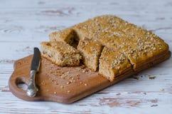 Eigengemaakte noten en honingscake met mes die dichtbij op houten oppervlakte liggen Stock Foto