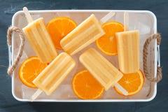 Eigengemaakte oranje ijslollys in een rustiek ijsdienblad stock foto's