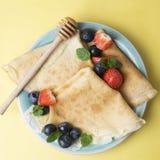 Eigengemaakte pannekoeken op een plaat met bosbessen en aardbeien Vierkant beeld Voedselfoto stock foto