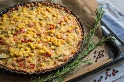 Eigengemaakte pastei met courgette, tomaten, kaas en graan op een dienblad, met verse rozemarijn en gekleurde peper stock fotografie