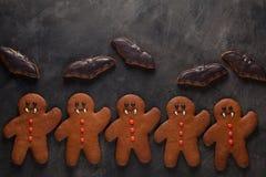 Eigengemaakte peperkoekkoekjes voor Halloween in de vorm van knuppels en van peperkoekmensen vampier op donkere concrete achtergr Stock Foto