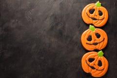 Eigengemaakte peperkoekkoekjes voor Halloween in de vorm van pompoenen op donkere concrete achtergrond met exemplaarruimte Hoogst Stock Foto's