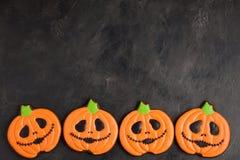 Eigengemaakte peperkoekkoekjes voor Halloween in de vorm van pompoenen op donkere concrete achtergrond met exemplaarruimte Hoogst Royalty-vrije Stock Afbeelding