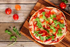 Eigengemaakte pizza met arugula en tomaten over hout Stock Afbeeldingen