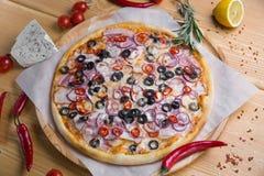 Eigengemaakte pizza met op een houten achtergrond met vruchten en groenten met kruiden royalty-vrije stock fotografie