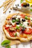 Eigengemaakte pizza met tomaten, olijven, salami, mozarellakaas en vers basilicum op een houten rustieke lijst royalty-vrije stock fotografie