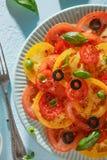 Eigengemaakte plantaardige tomatencarpaccio op blauwe plaat met vork op blauwe achtergrond Royalty-vrije Stock Fotografie
