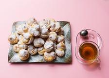 Eigengemaakte profiteroles dienden op een plaat met een kop thee op een roze achtergrond Vlak leg stock fotografie