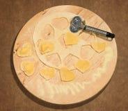 Eigengemaakte ravioli in de vorm van hart, met ruwe deeg en wielsnijder die op een rond belangrijkst voorwerp in hout wordt gepla Royalty-vrije Stock Afbeeldingen