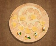 Eigengemaakte ravioli in de vorm van hart, open en gesloten, op een rond belangrijkst voorwerp in hout Royalty-vrije Stock Foto's