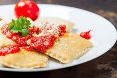 Eigengemaakte ravioli met tomatensaus, peterselie en parmezaanse kaaskaas op een witte plaat Stock Foto