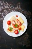 Eigengemaakte ravioli met tomatensaus, peterselie en parmezaanse kaaskaas op een witte plaat Stock Afbeeldingen