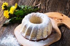 Eigengemaakte ringscake met suikerglazuursuiker op een landelijke houten raad Stock Fotografie
