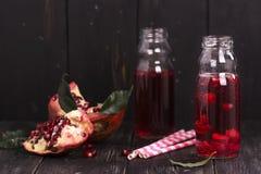 Eigengemaakte rode granaatappellimonade in kleine glasflessen Royalty-vrije Stock Afbeelding