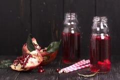 Eigengemaakte rode granaatappellimonade in kleine glasflessen Royalty-vrije Stock Foto's