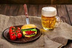 Eigengemaakte rundvleeshamburger en verse groenten op Kleischotel met glas Royalty-vrije Stock Foto's